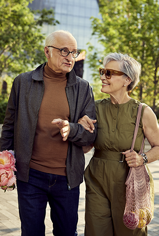Couple enjoys an outdoor walk downtown near their Coterie Senior Living residence.