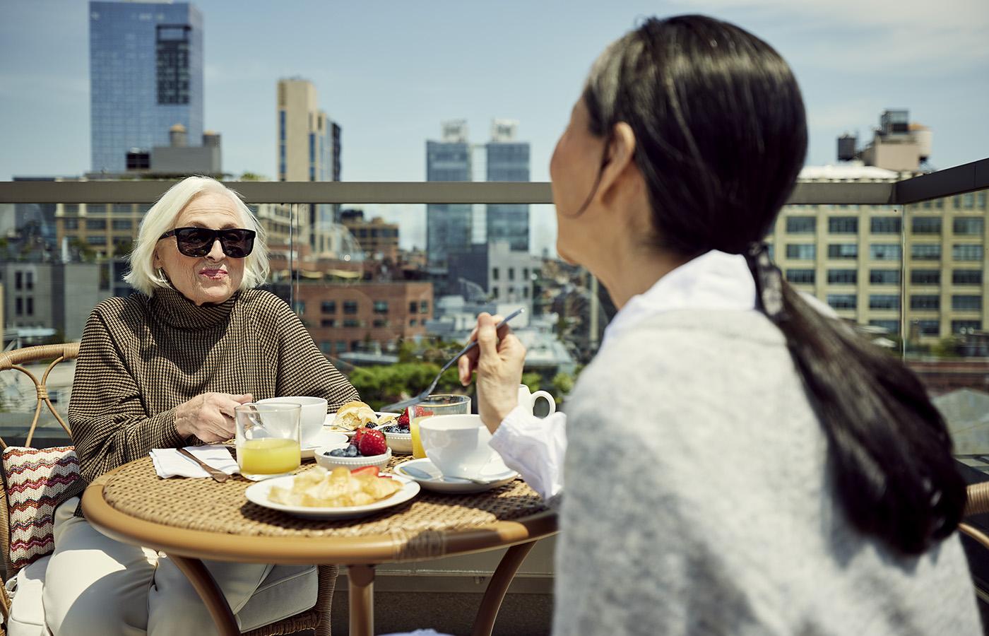 Women enjoying brunch outside at Coterie - a luxury senior living residence.